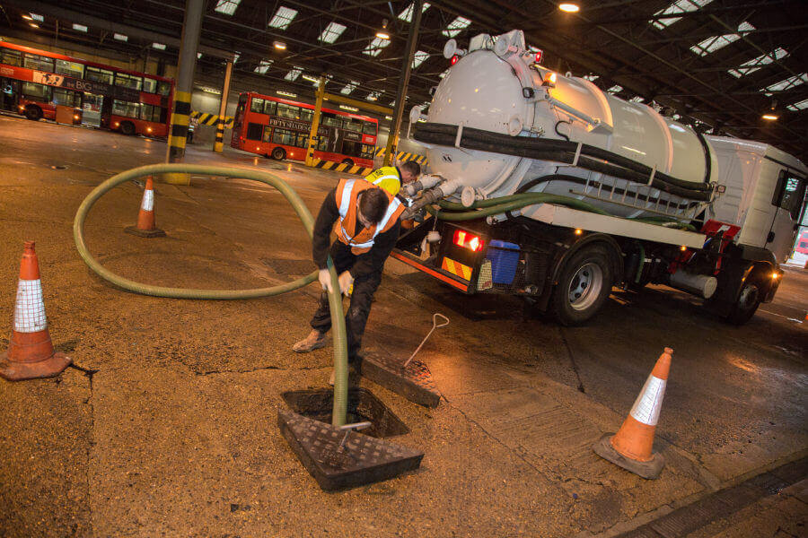 Engineer extracting liquid waste with tanker