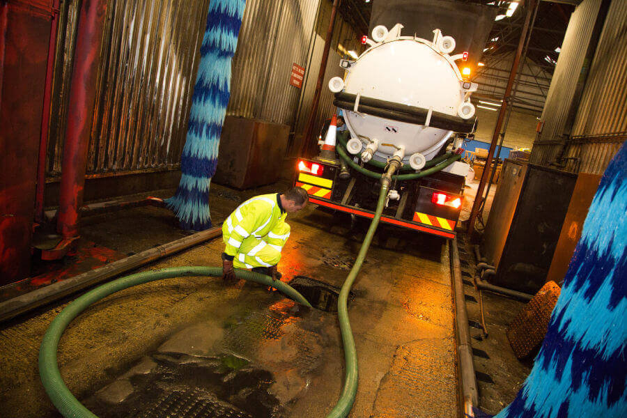 Vacuum tanker extracting at bus station
